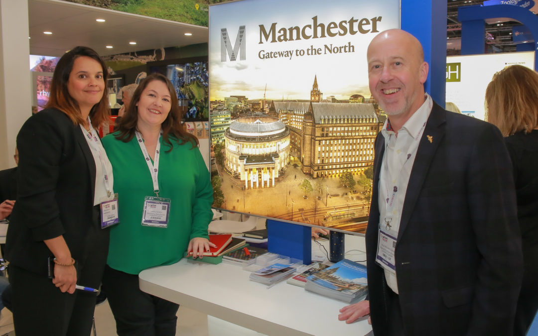 Three people stand around a sign showing Manchester's town hall and Central Library. The sign reads, Manchester: Gateway to the North.